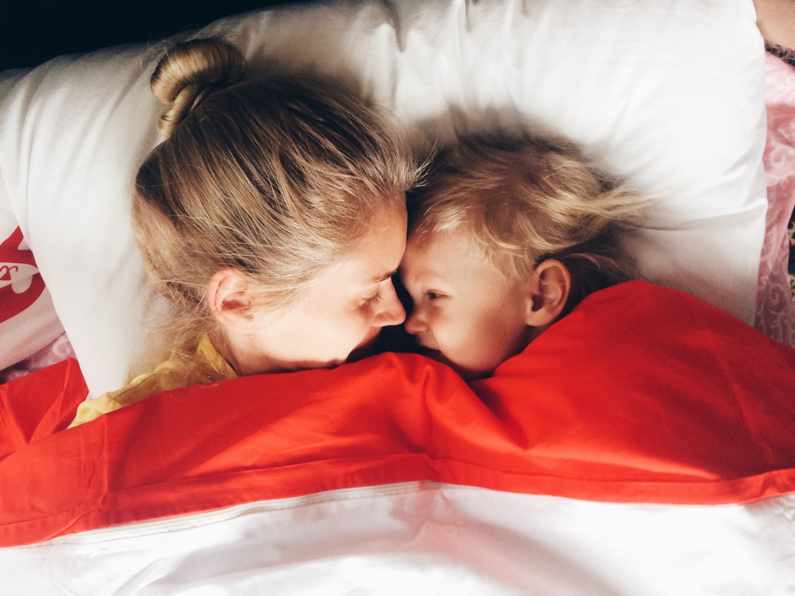 mother and child in bed laughing together