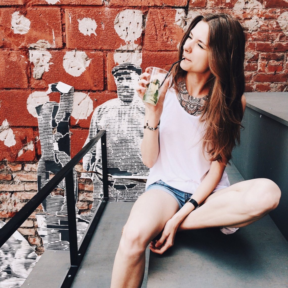 girl sipping on fruity drink relaxing by street art