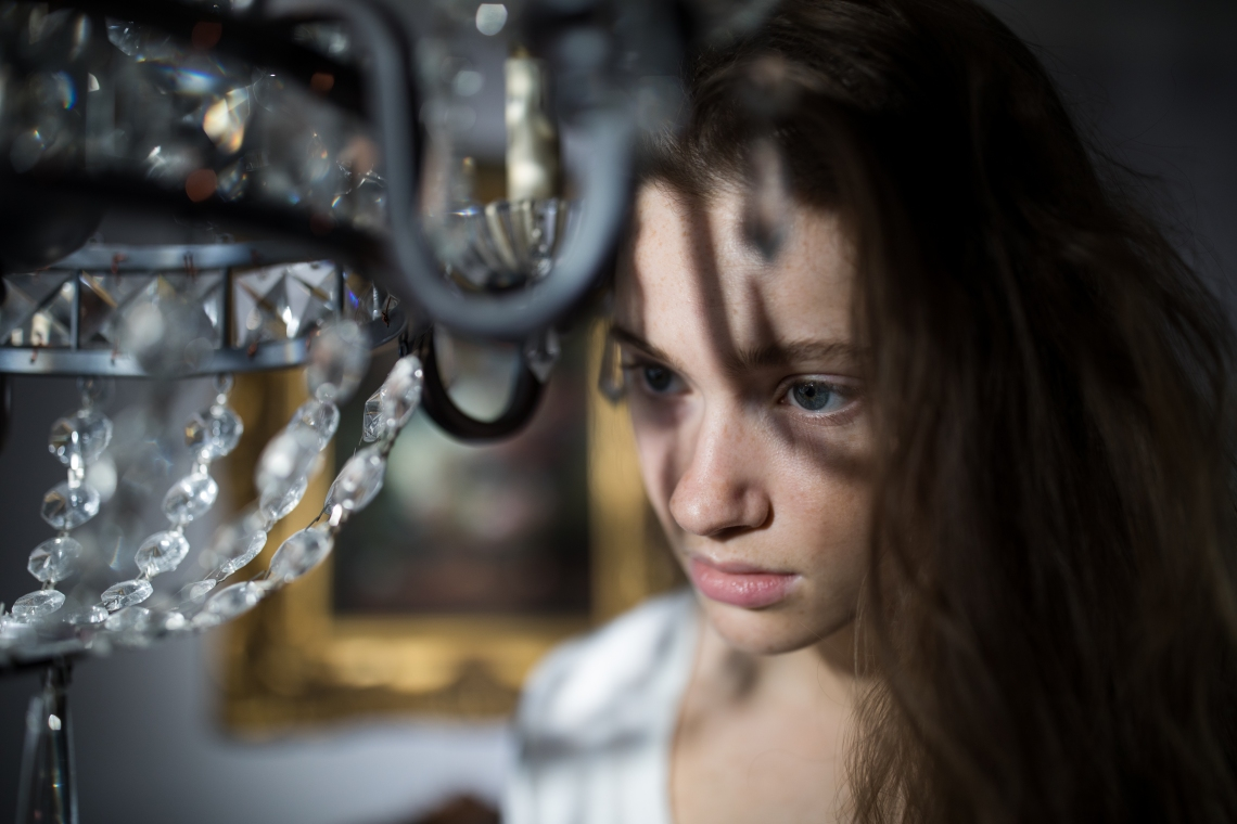 woman looking sad by chandelier