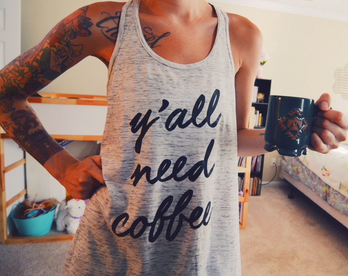 girl drinking coffee in the morning wearing a y'all need coffee tank top