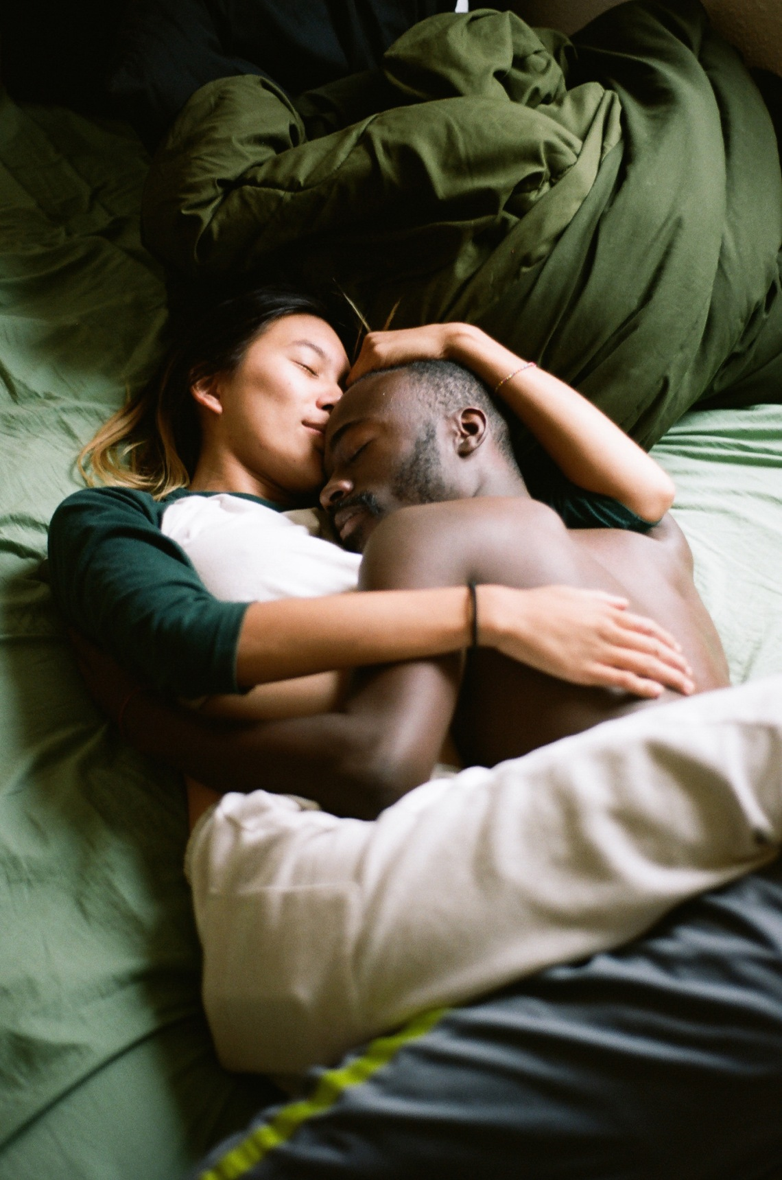 Man and woman embracing, intimate in bed, in love, comforting, cradling, taking care of each other