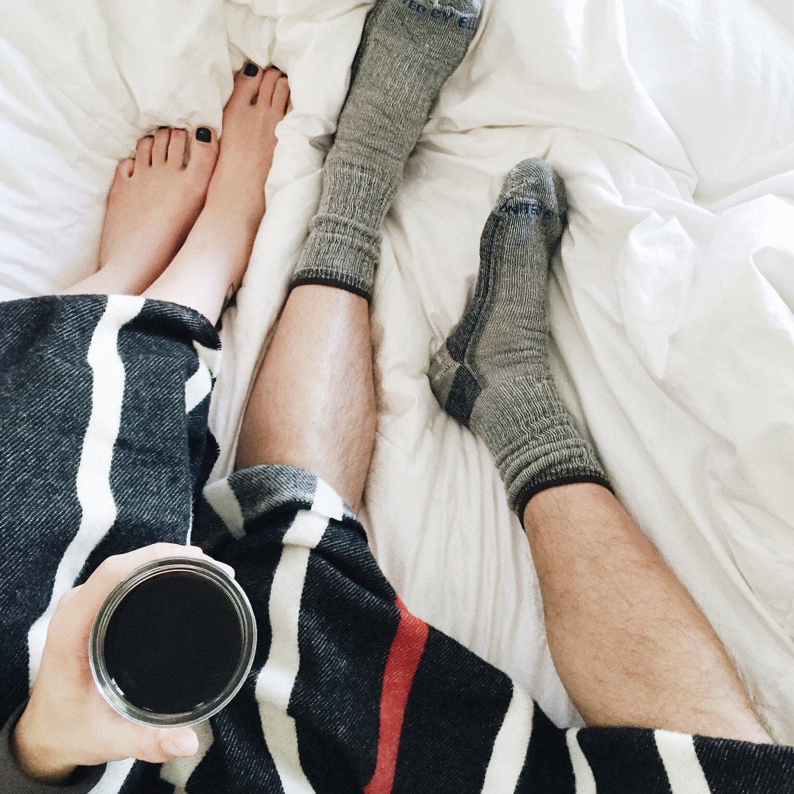 couple in bed tangled sheets with coffee and a blanket