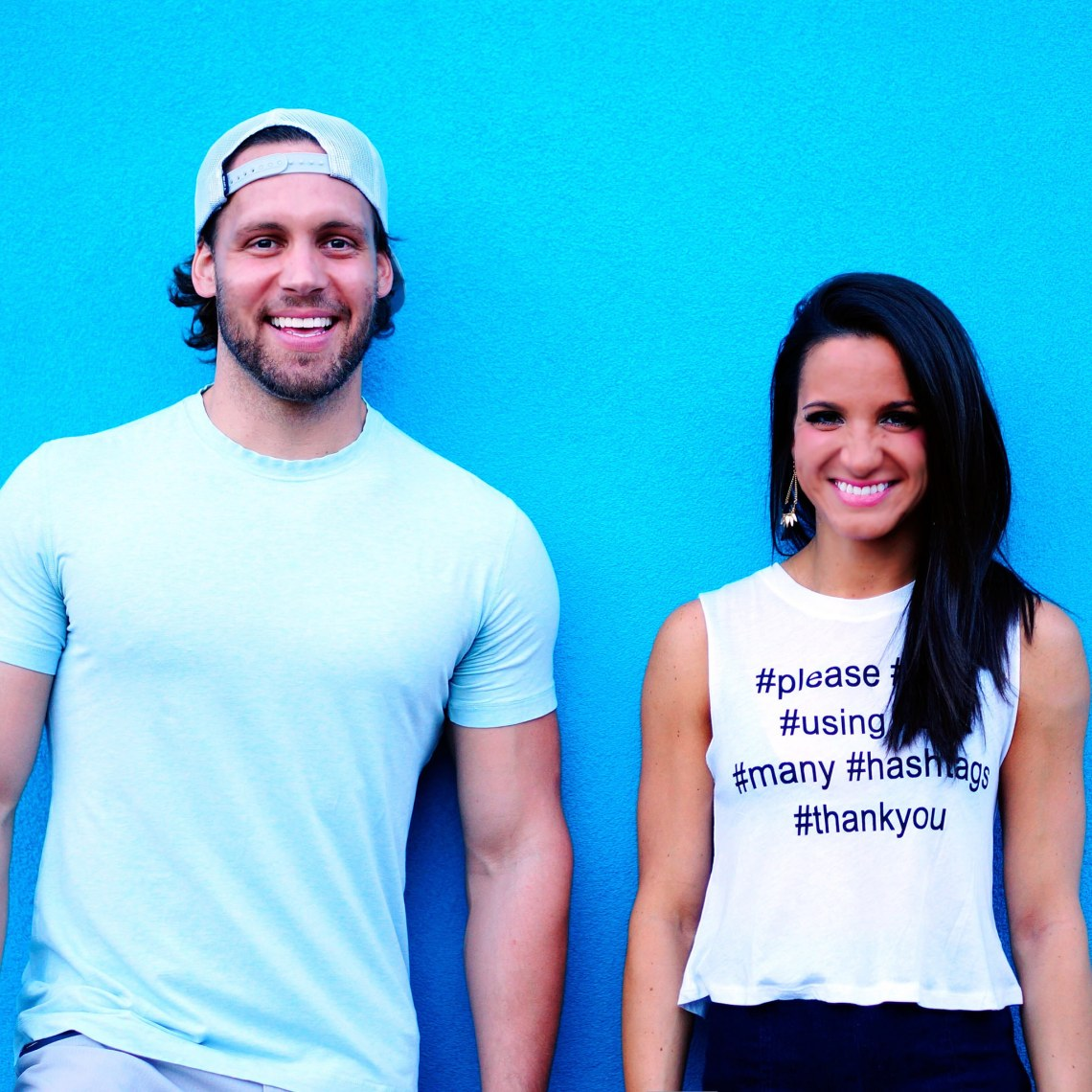 couple or friends hanging out against blue wall with hashtag shirt on