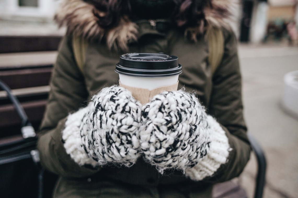 girl holding coffee in winter with gloves on and winter coat