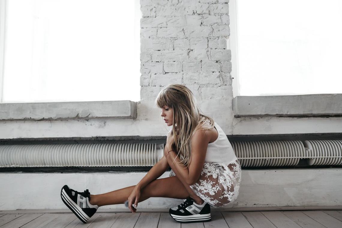 Girl in a sheer white skirt and heavy chunky sneakers contemplating life, thoughtful, pensive, brave