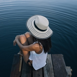 Woman sits on a doc, staring out at the water