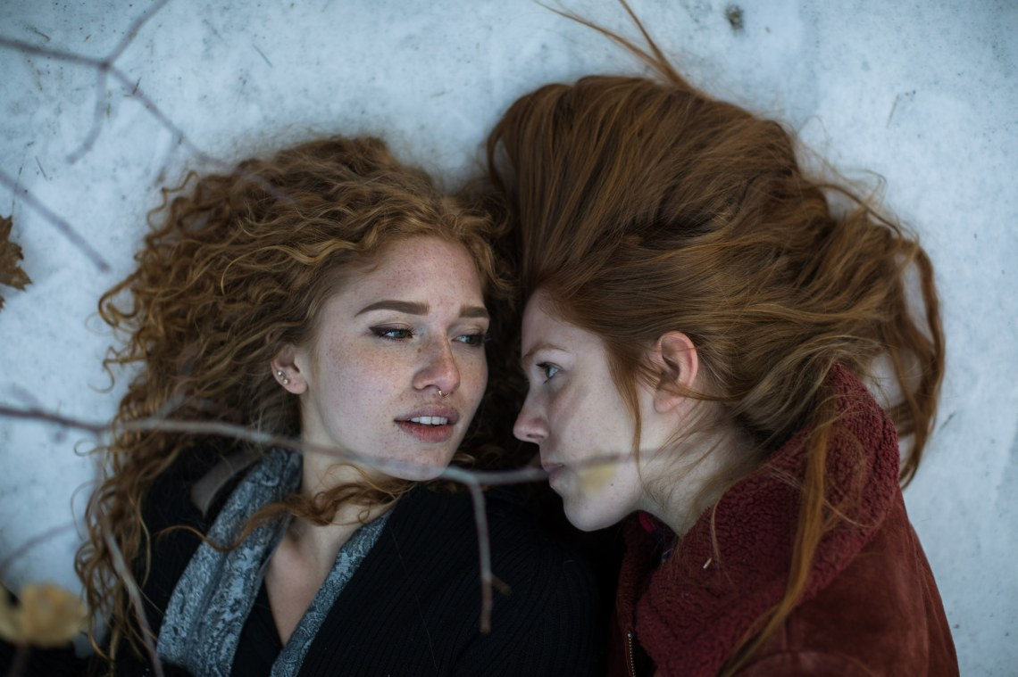 two women lock eyes as they lay together on the snowy ground