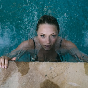 Beautiful woman pulls herself up on the ledge of a swimming pool as she emerges from the water