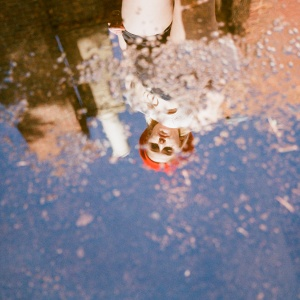 woman standing looking at self in puddle