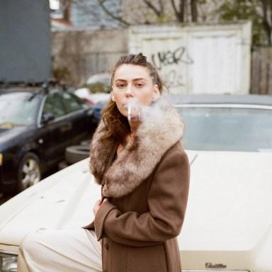 girl smoking next to a car