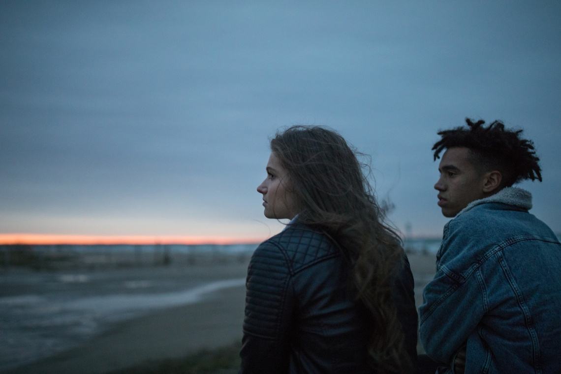 young couple on beach sad