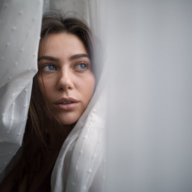 woman looking thoughtful in curtains