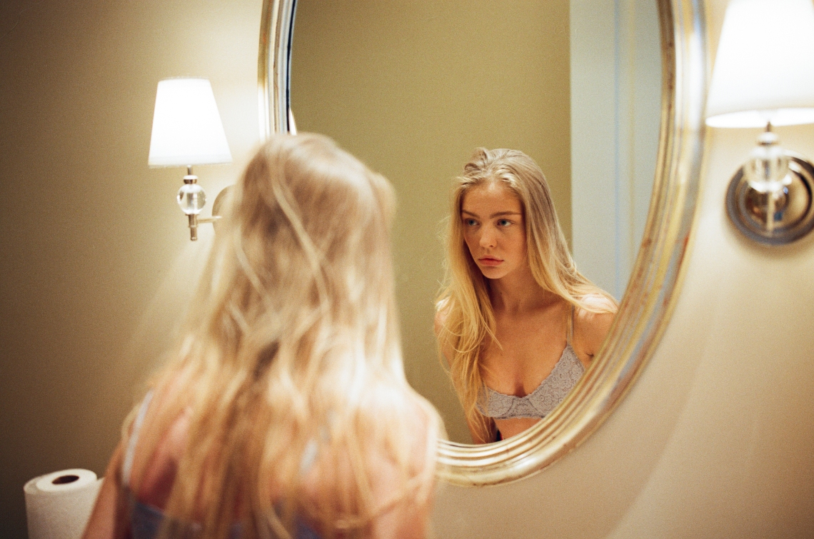 woman staring in mirror