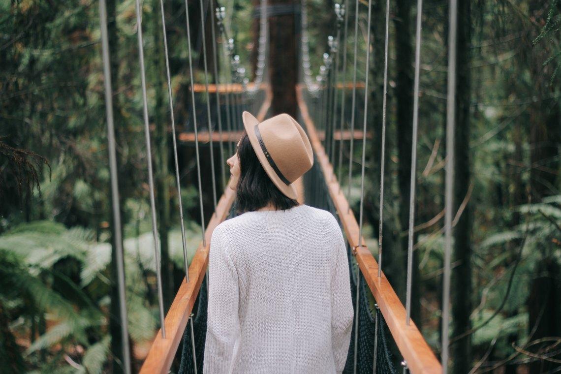 Woman walking over bridge in forest