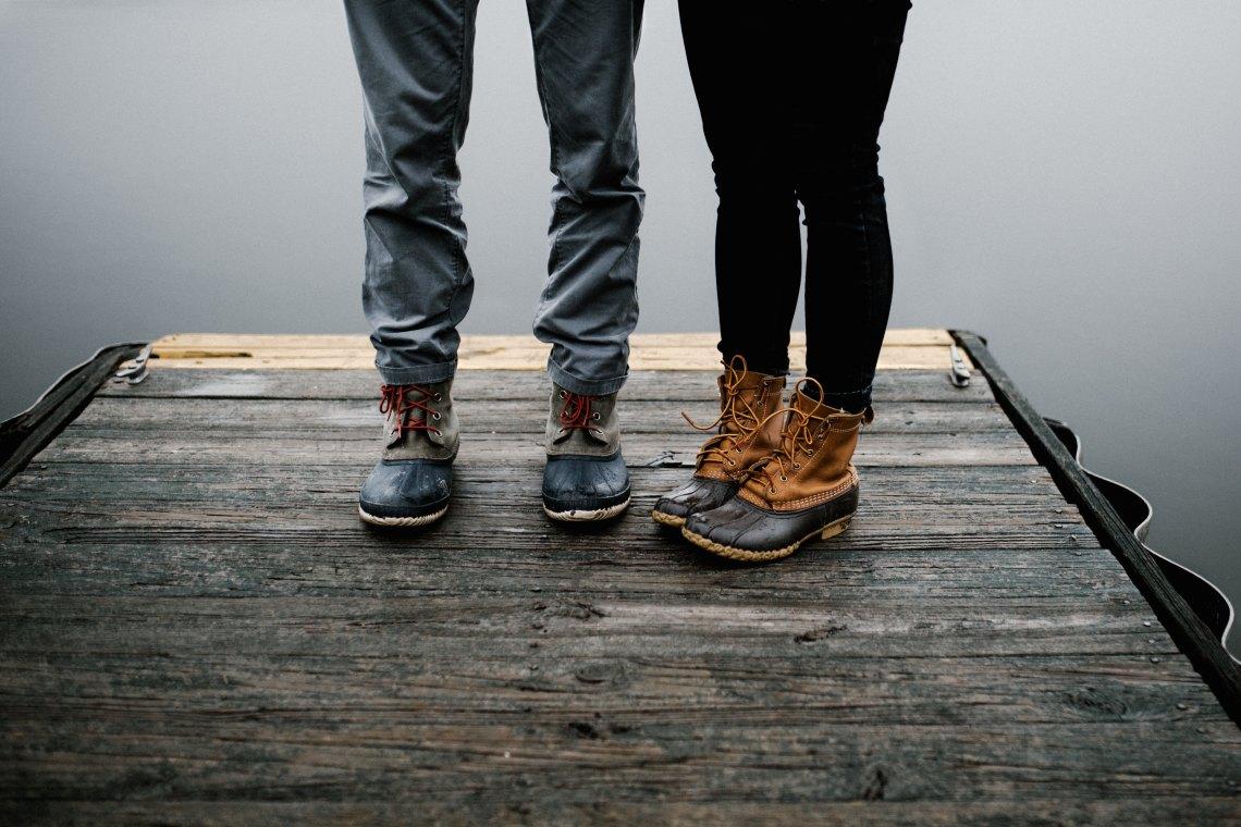 Couple's feet standing on dock
