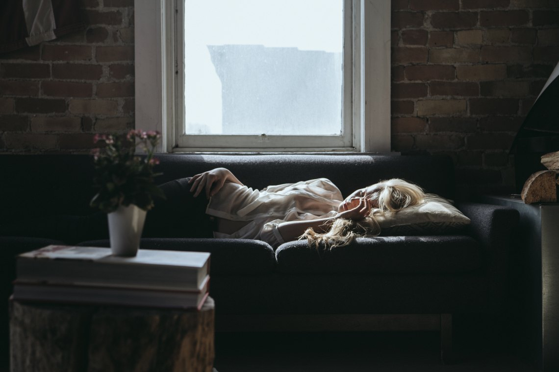 depressed woman sleeping on couch