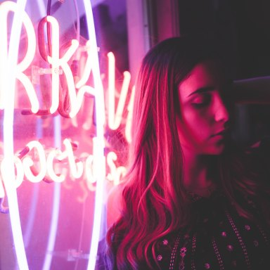 woman next to neon