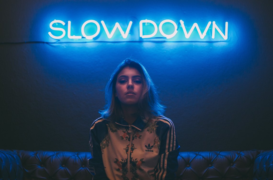 Woman standing under neon sign