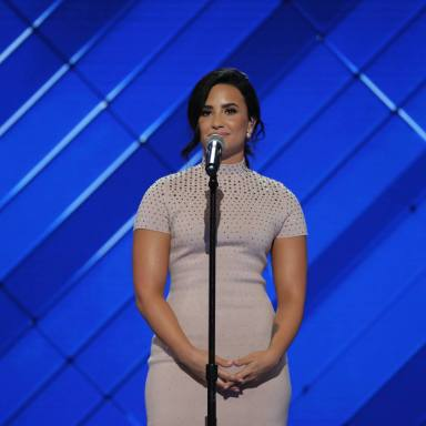 Demi Lovato stands on stage where a white dress in front of a blue background for some event