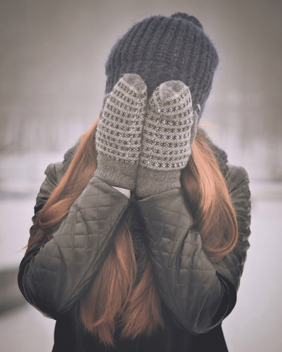 woman hiding face in mittens