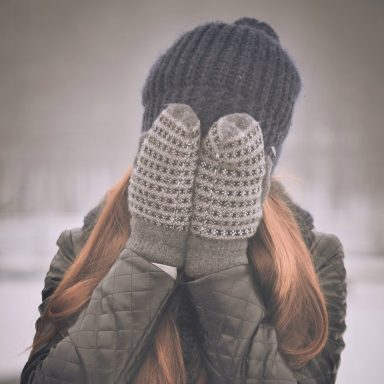 woman covering face with mittens