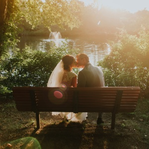 Wedding couple kissing on bench