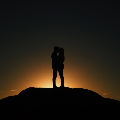 Man and woman stand in the dark on the horizon holding each other close