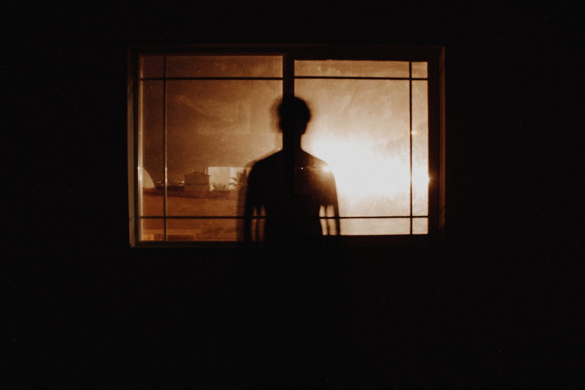 creepy photo man standing in front of window