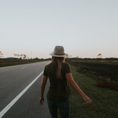 woman walking alongside road