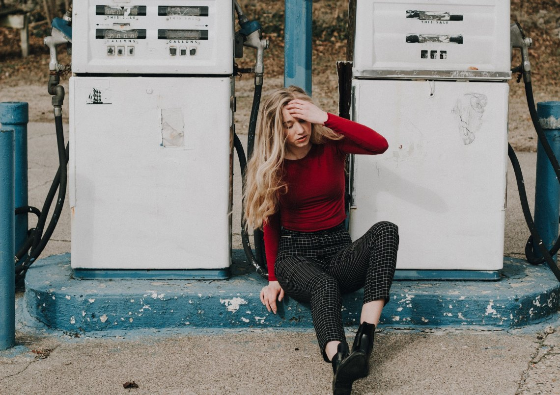 woman sitting by gas pumps