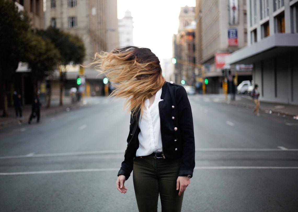 woman standing in street hair blowing in wind