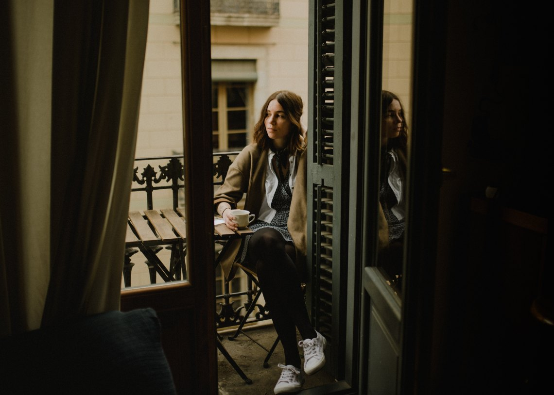 girl sitting on balcony looking contemplative