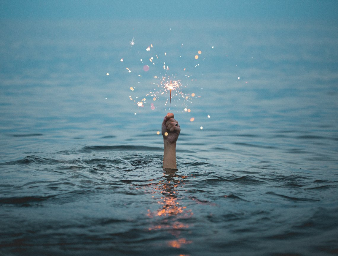 hand with sparkler in water