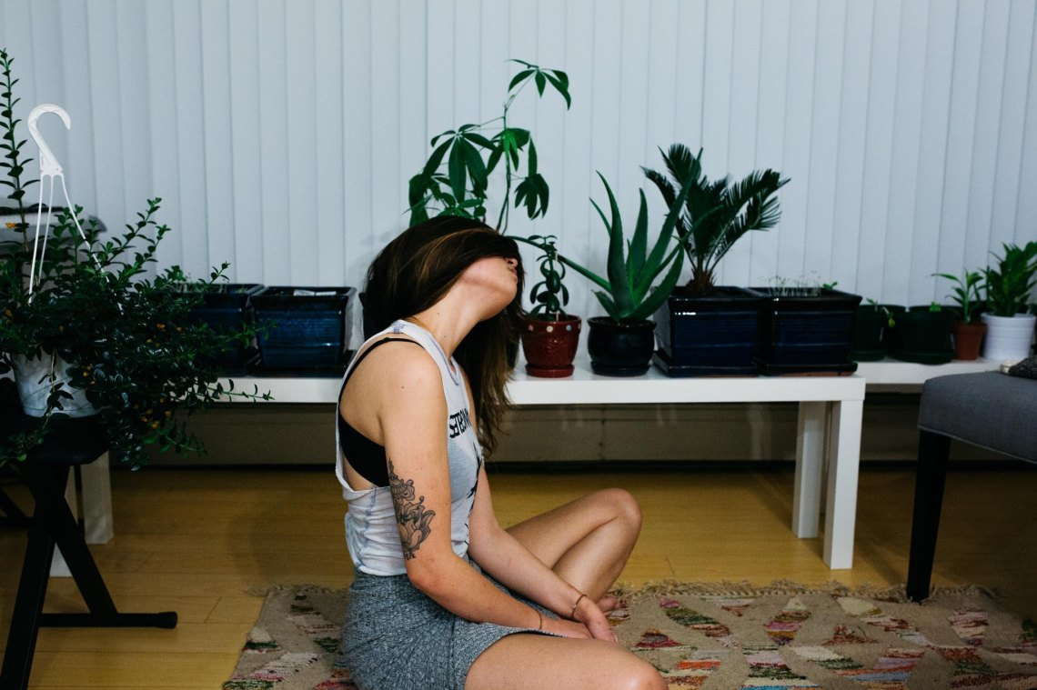 girl sitting on the floor of an apartment near plants