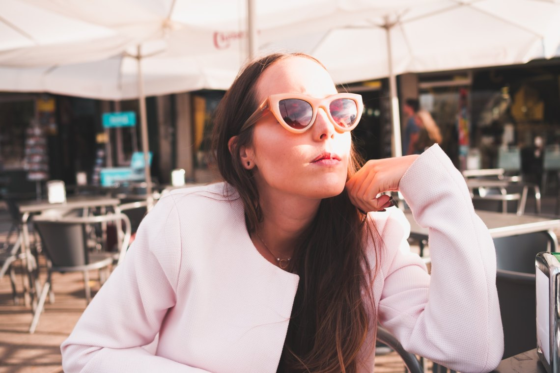 girl in a white jacket with sunglasses
