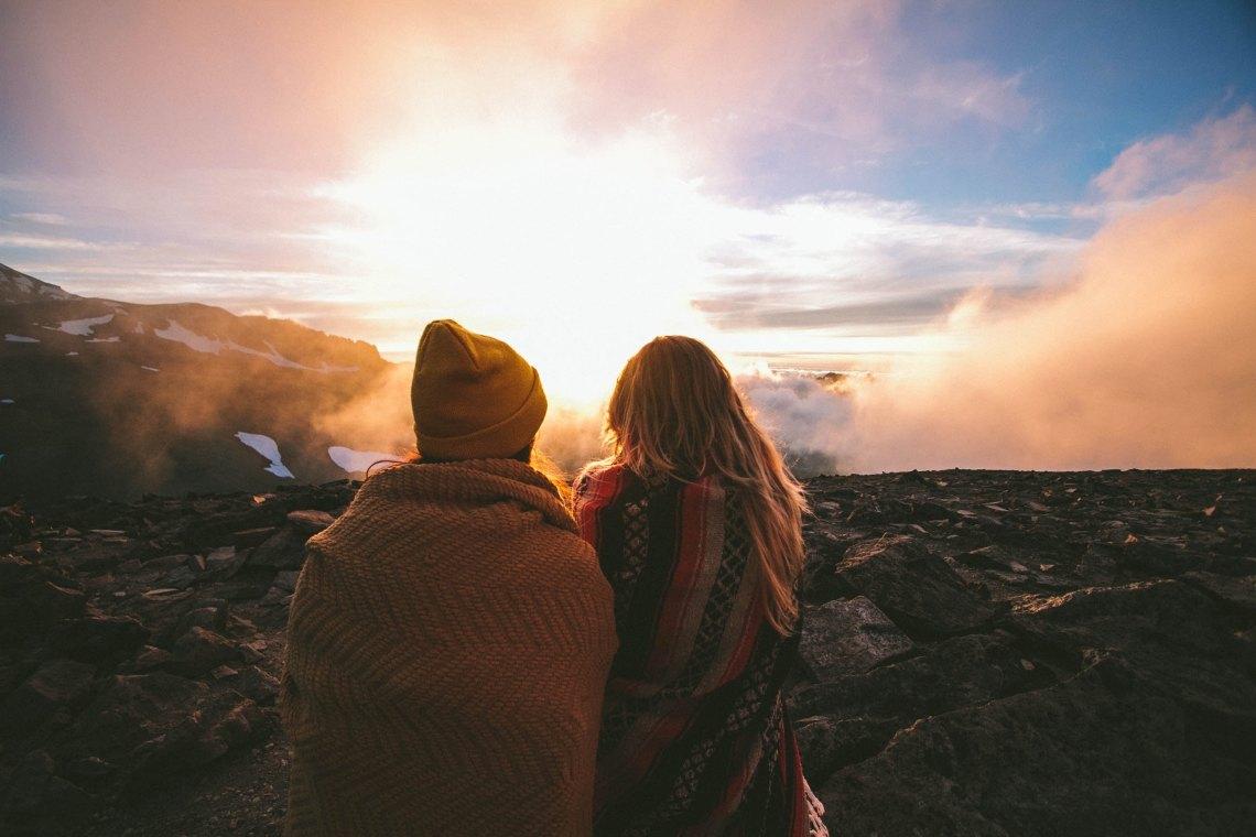 couple sitting on cliff, happy couple, apology language, apologies, love, zodiac sign