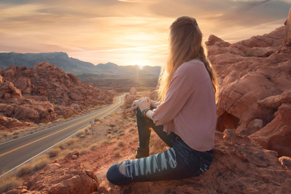 woman sitting on rocks at sunset