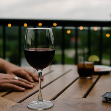 person with red wine on porch