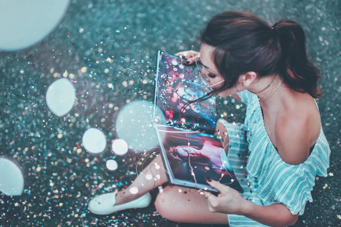 Girl looking at neon book
