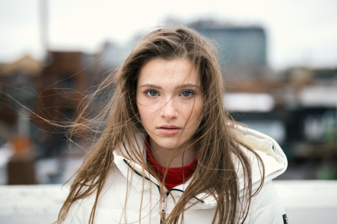 girl with a white coat and hair in her face