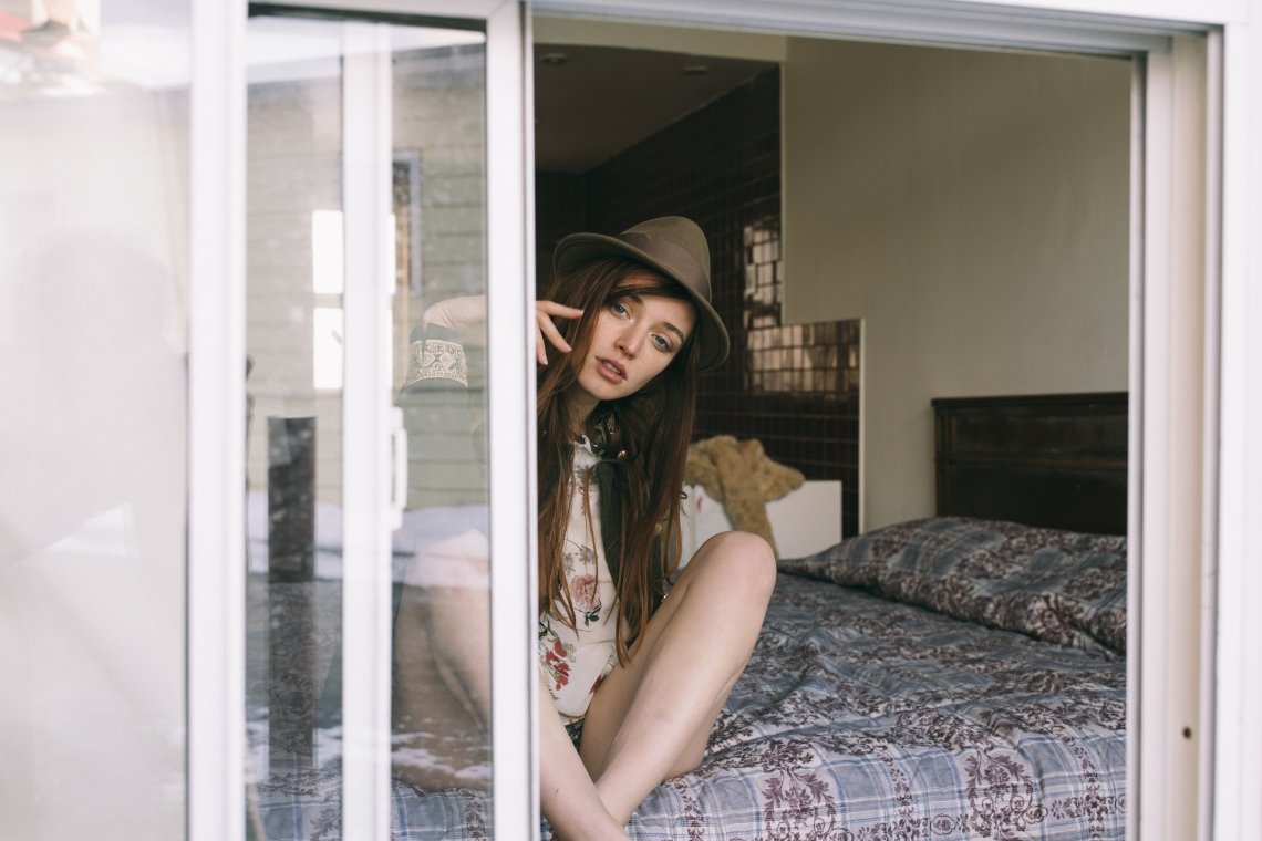 woman peering out window while sitting on bed