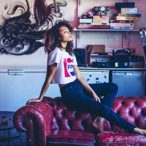 Young woman in Pepsi cropped tee t-shirt sitting on red leather couch, vintage board games