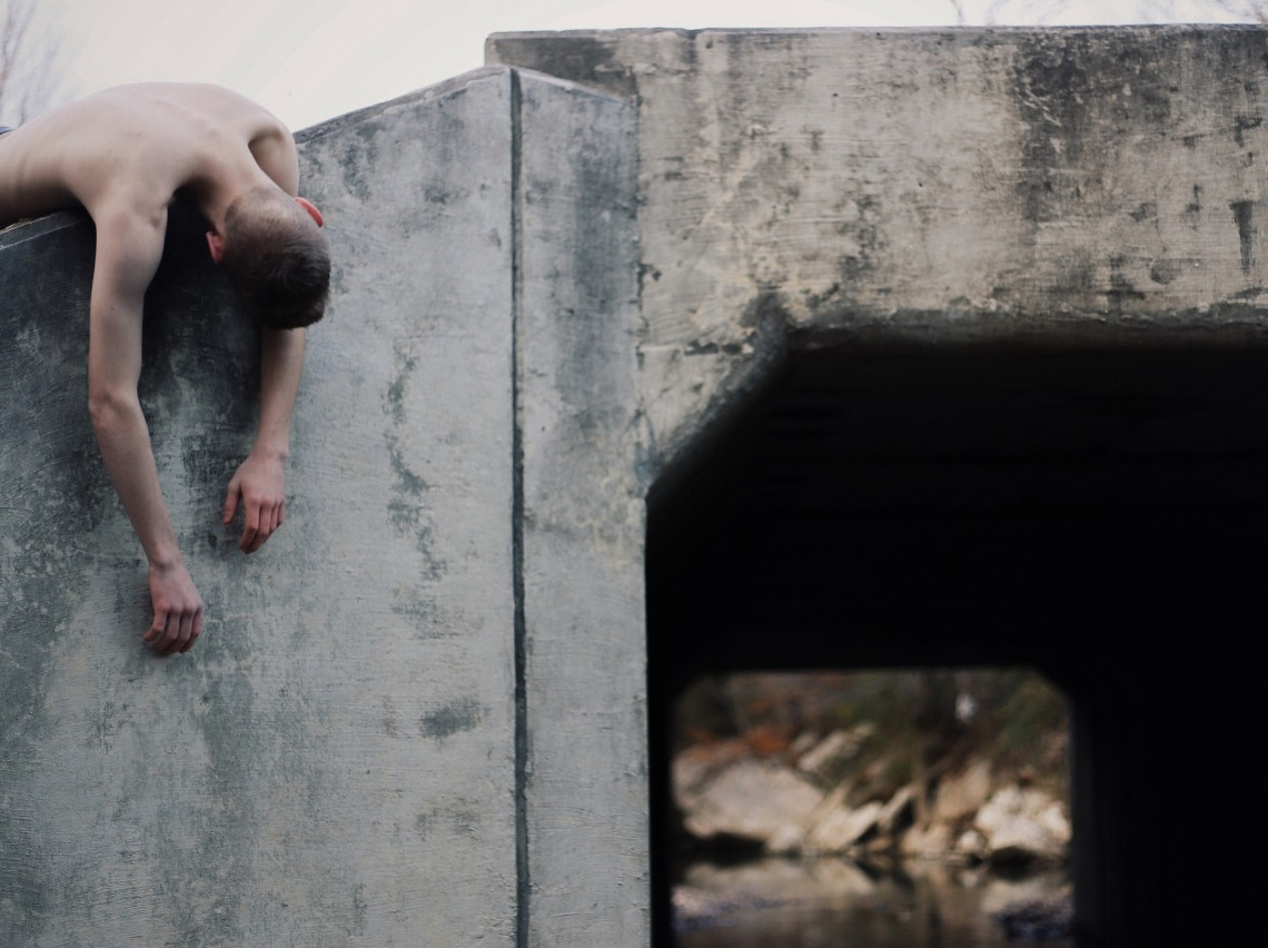 Shirtless man draped over concrete wall of bridge, possibly creepy