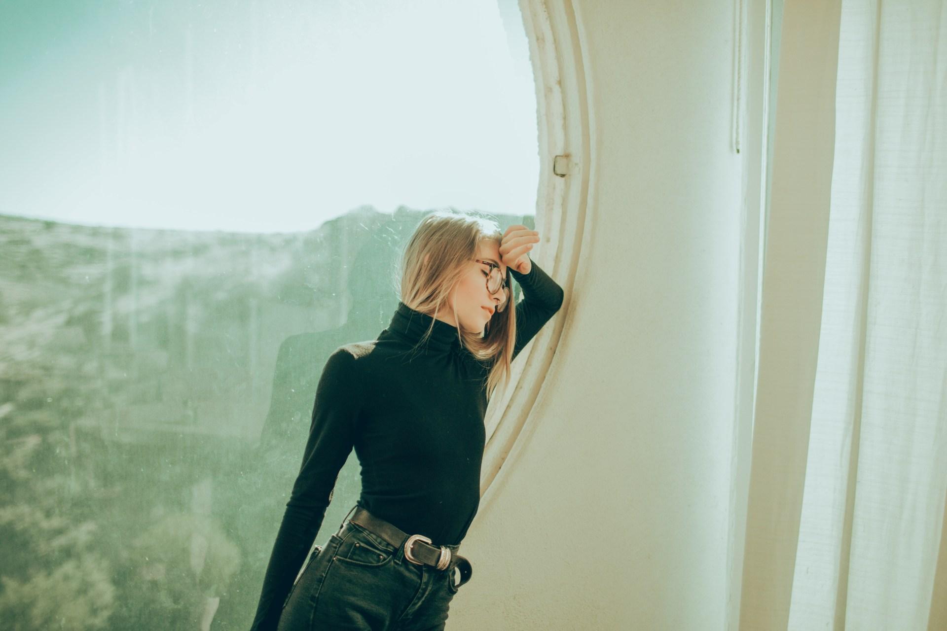 woman leaning by window