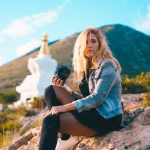 Blonde woman with camera contemplating her next photo op, sitting on a rock