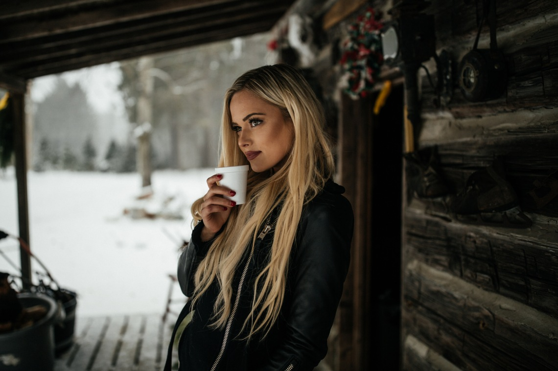 Blonde woman thinks about her life in winter while drinking a warm beverage