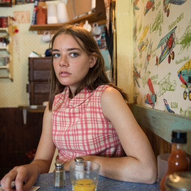 woman sitting in diner looking scared