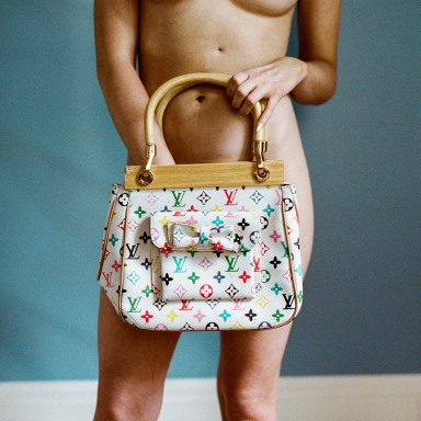 A woman stands naked in front of the camera, holding nothing but a purse to hide her