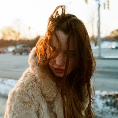 Pretty woman in a fur coat with her hair in her face