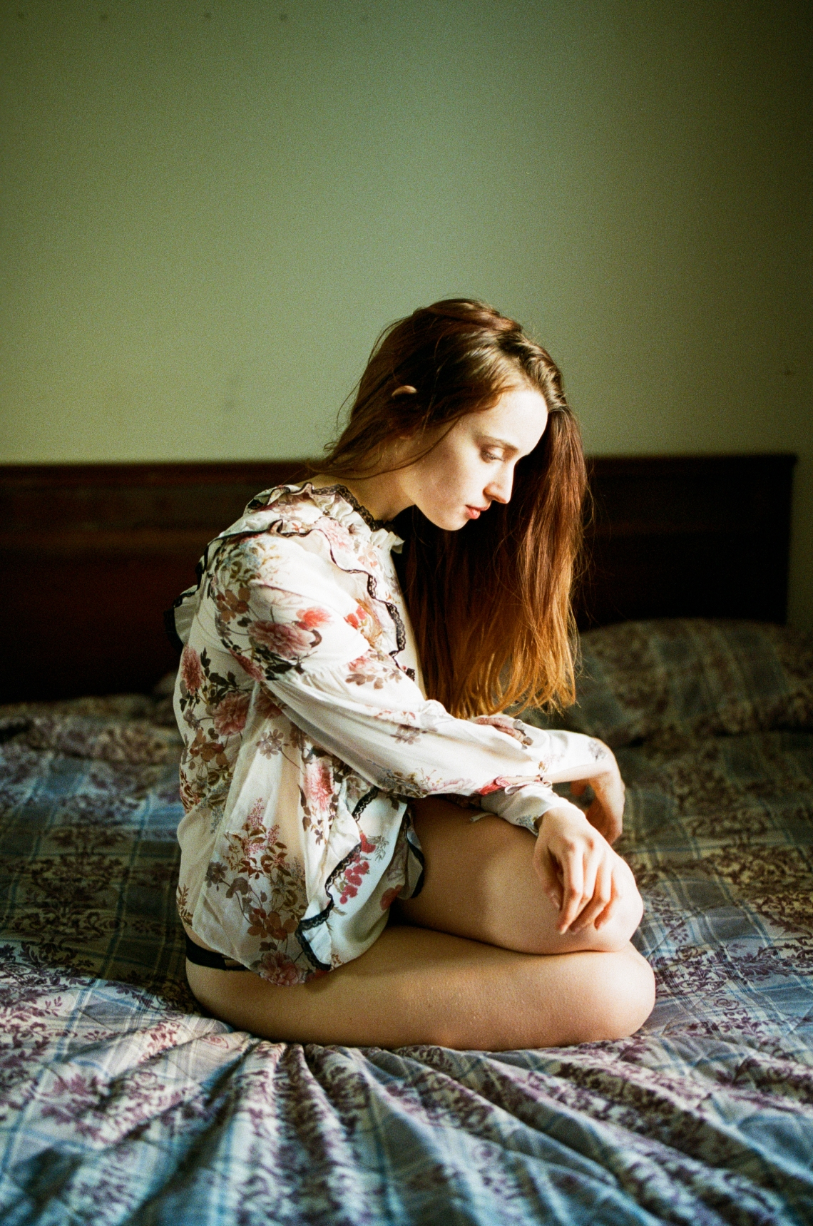 woman sitting on bed looking thoughtful